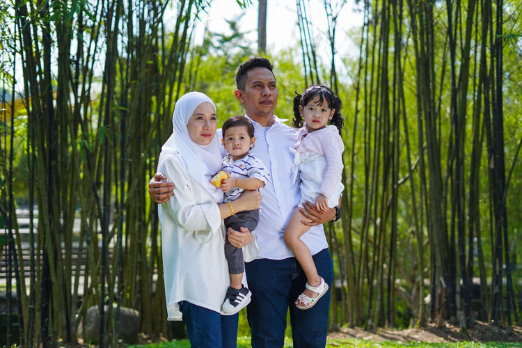Playful family spending time together at park. Group Of People Men Standing Togetherness Child Childhood Family Males  Parent Boys Father Son Plant Offspring Females Bonding Tree Mother Women Smiling Daughter Outdoors
