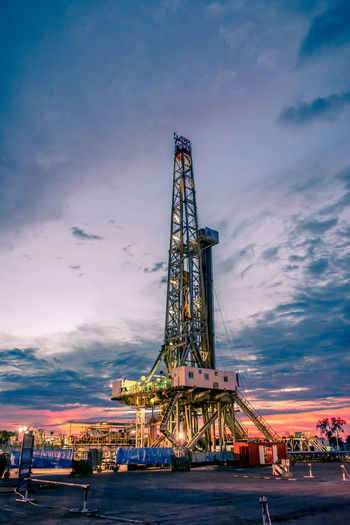 Low angle view of drilling rig against sky during sunset
