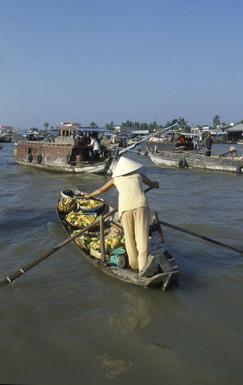 Rear view of female fruit vendor oaring boat in river against clear sky