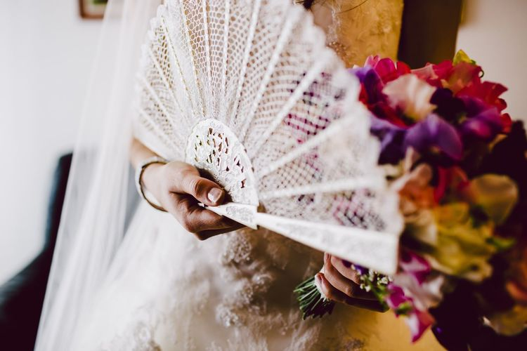 Midsection of bride holding fan and flower bouquet