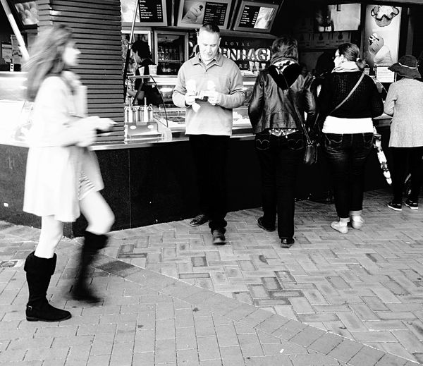 Capturing Motion People, Strangers, black and white, men, women,general public, ice cream stand, city, adults, group, human behaviour, walking, striding, motion, Real People Lifestyles Outdoors Day food vendor,