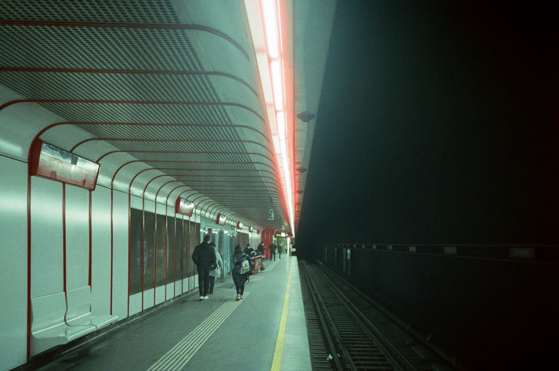People in illuminated railroad station at night