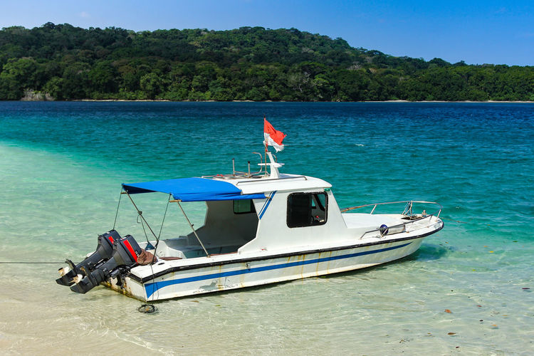 Boat resting on a clear beach INDONESIA National Park Beauty In Nature Blue Day Flag Mode Of Transportation Nature Nautical Vessel No People Outdoors Patriotism Plant Scenics - Nature Sea Sky Transportation Travel Tree Tropical Island Ujung Genteng Beach Ujung Kulon Vacation Water