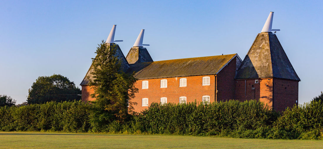 Oast House, Kent Hop Fields ,Faversham,Kent Beer Farm Kent Oast House Shepherd Neame United Kingdom Architecture Brewery Brewing Built Structure Clear Sky Day Hop Pole Hops Nature No People Outdoors Plant Rural Scene School Sky Tourism Travel Destinations Tree Village