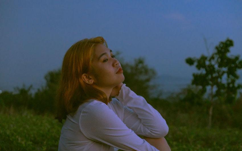 Portrait of woman looking away on field against sky