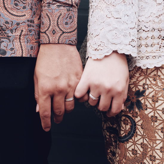 Midsection Of Couple Wearing Rings