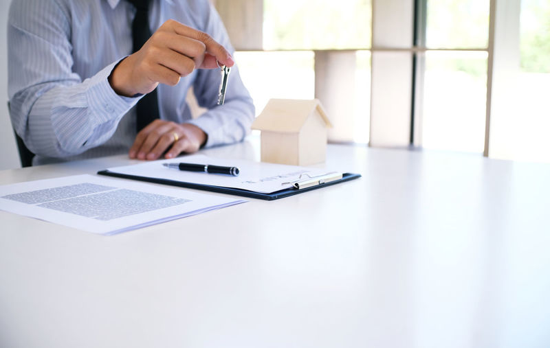 Midsection Of Insurance Agent Holding Key By Documents On Desk