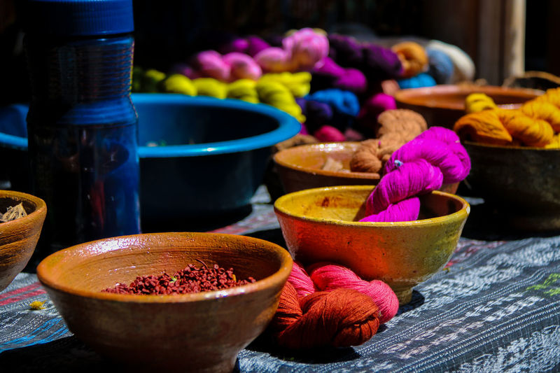 Close-up of colorful strings in bowls on table