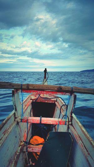 Boat at sea shore against sky