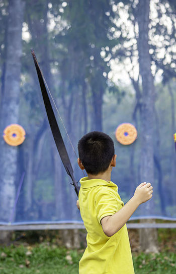 Side view of boy practicing archery in park