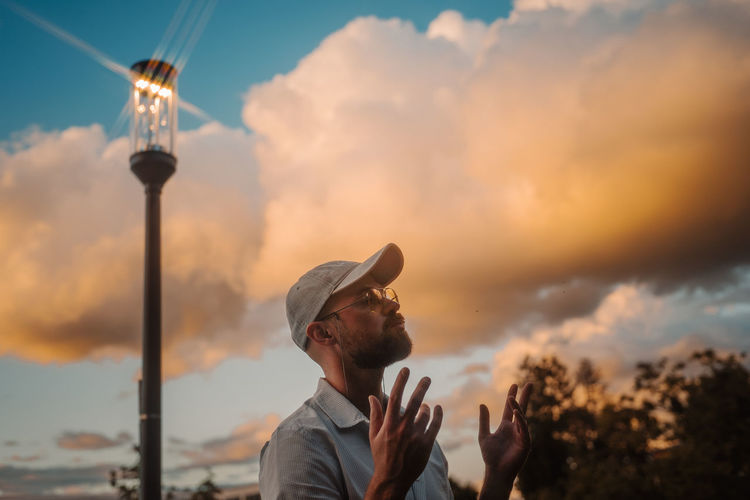 Portrait of young man standing against sky during sunset