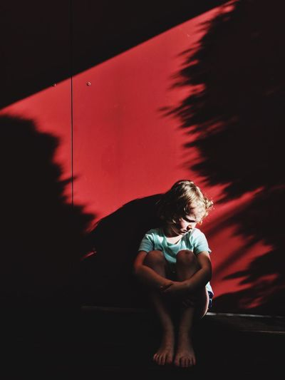 Sad Boy Sitting Against Red Wall With Sunlight
