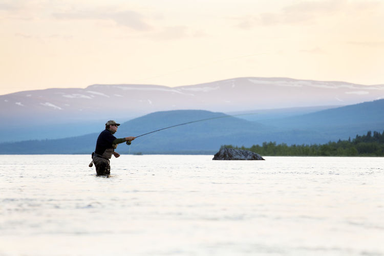 Man fishing in lake against mountains
