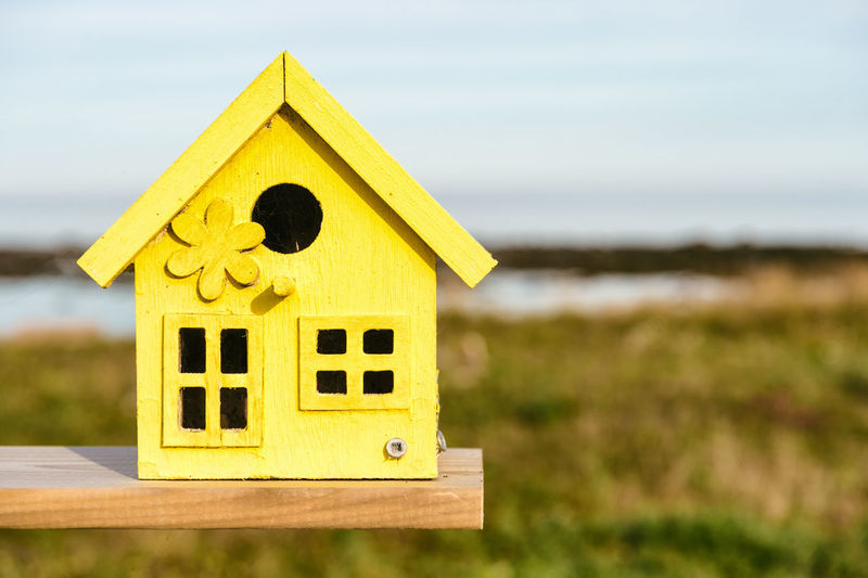 Close-up of yellow wooden birdhouse on field