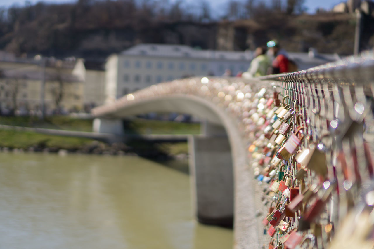selective focus, day, river, outdoors, architecture, bridge - man made structure, water, built structure, love lock, real people, building exterior, city, tilt-shift, close-up
