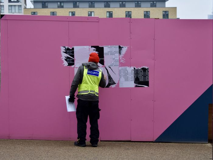 A security guard removing posters Security Adult Adults Only Architecture Building Exterior Cap Casual Clothing Day Full Length Hardhat  Headwear Hooded Shirt Lifestyles Men Mid Adult Men One Man Only One Person Outdoors People Pink Color Real People Standing Uniform Warm Clothing Young Adult The Photojournalist - 2018 EyeEm Awards The Troublemakers The Street Photographer - 2018 EyeEm Awards