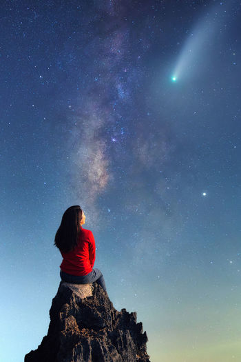 A young woman watching the beauty of the milky way and a meteor on the rocks.