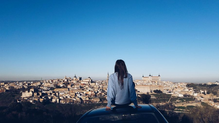 Rear view of woman looking at cityscape while sitting on car roof against clear blue sky
