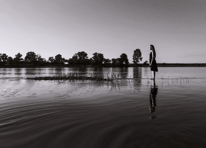 Girl standing in lake against sky