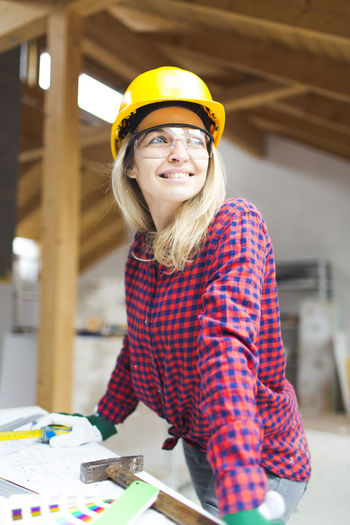 Portrait of smiling woman standing at construction site