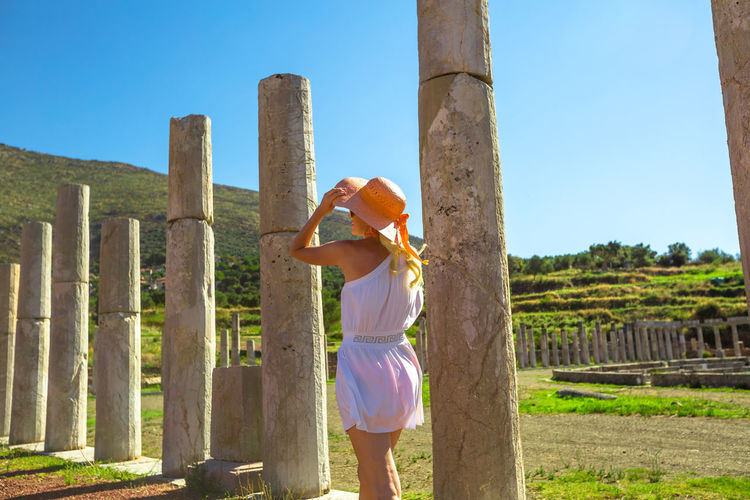 Rear view of woman standing against columns during sunny day