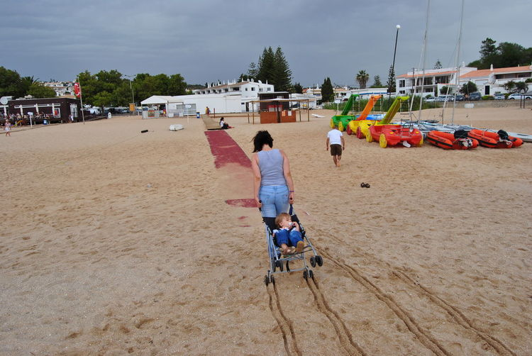 Rear view of mother pulling carriage with son at sandy beach