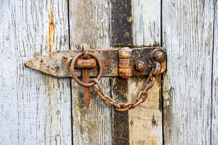 Rusty chain and lock on a wooden door
