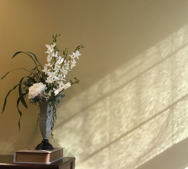 Close-up of vase on end table against the wall