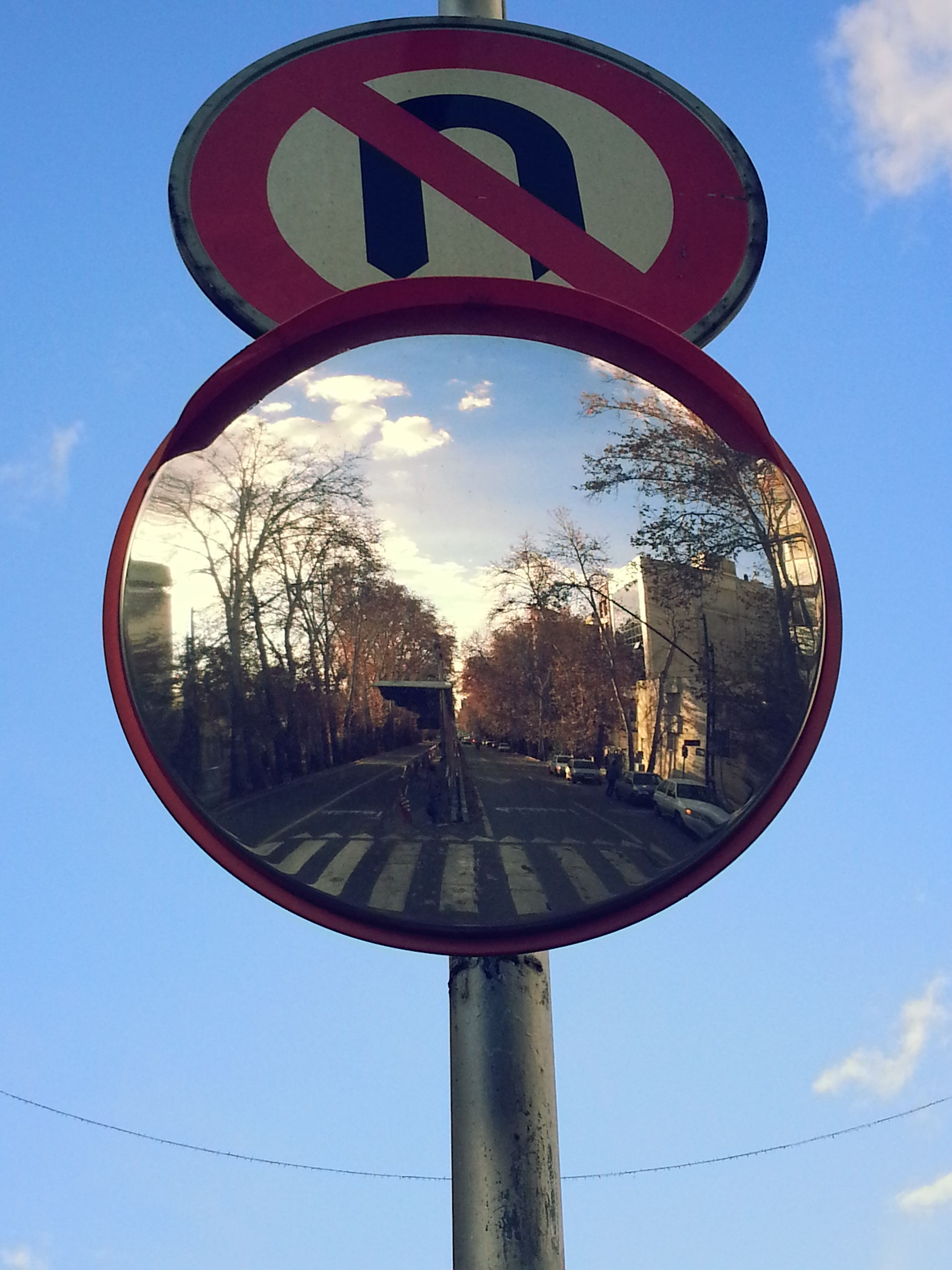 sky, circle, reflection, tree, transportation, cloud - sky, cloud, geometric shape, side-view mirror, day, round, outdoors, blue, no people, wheel, mirror, metal, built structure, field, close-up