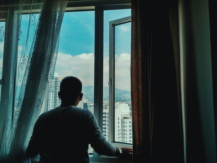 Rear View Of Man Standing Amidst Curtains At Window