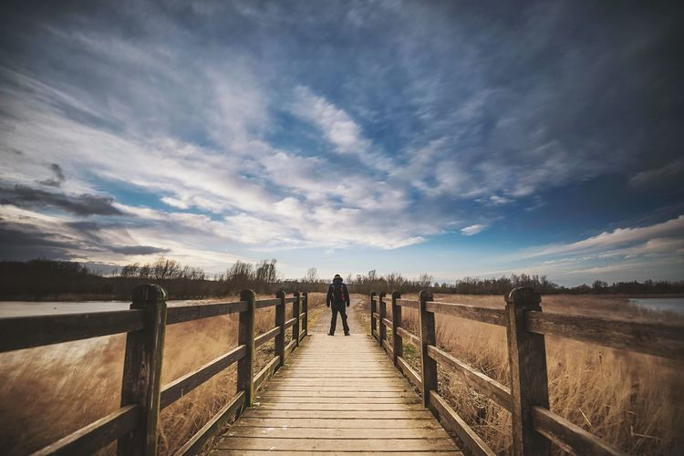 Rear view of man standing on boardwalk against cloudy sky