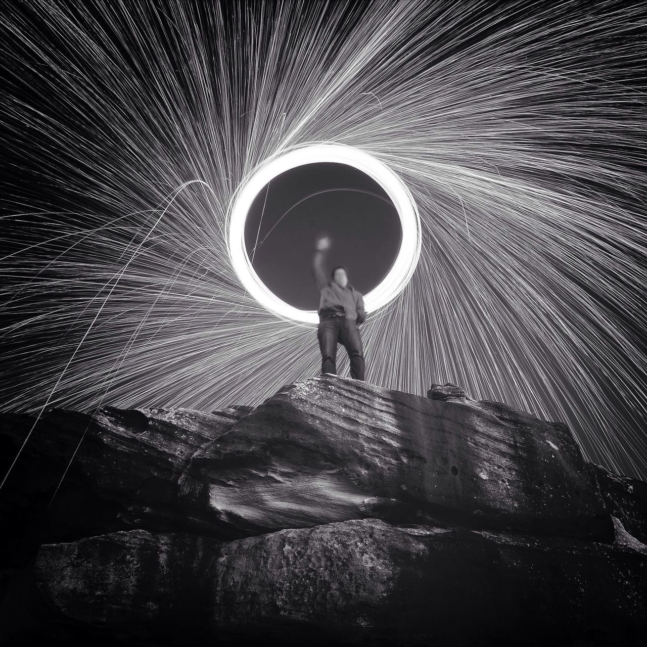Low angle view of man spinning steel wool on rock at night