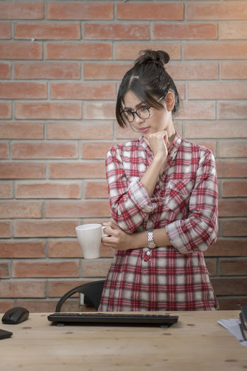 Businesswoman Looking Away While Standing Against Brick Wall