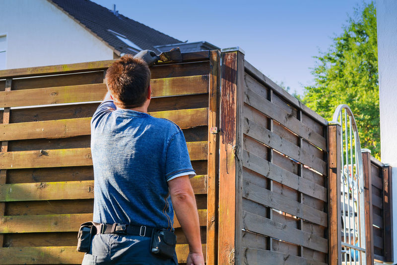 Rear view of man painting wooden fence