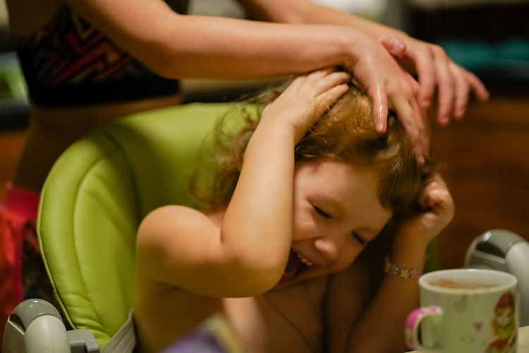 Midsection of girl massaging cheerful sister head at home