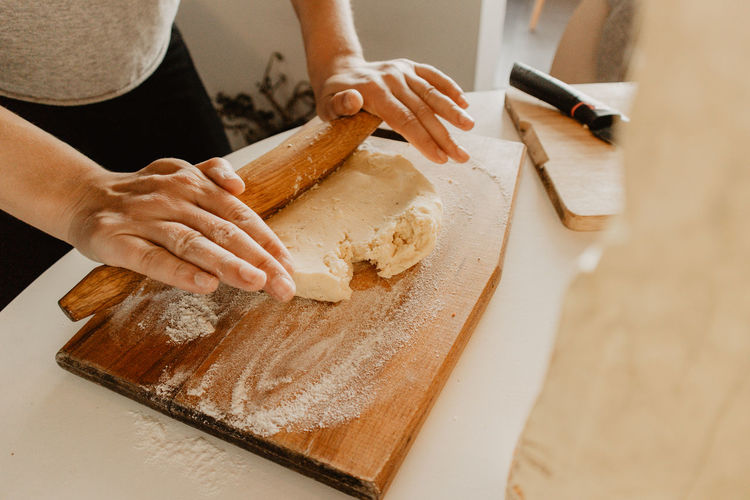 Midsection of woman rolling dough