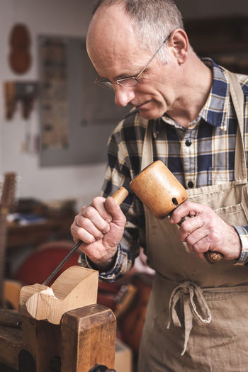 A mature man is working with carving tools on a piece of wood. He is wearing an apron and a checkered shirt standing inside a workshop. One Person Indoors  Holding Occupation Work Tool Workshop Real People Working Skill  Mature Men Craft Craftsperson Glasses Mature Adult Men Carving Chisel Mallet Apron Wood - Material Carpentry Art Artist Artisan
