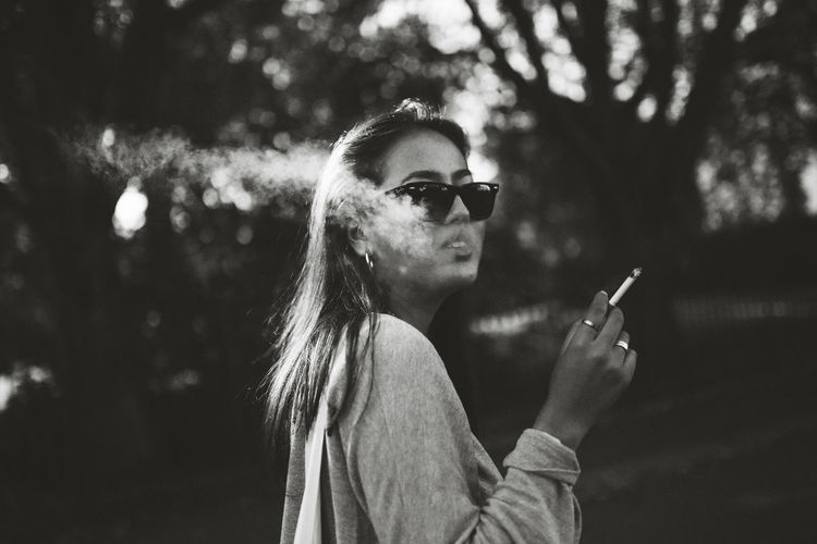 Side view of young woman smoking while looking at camera