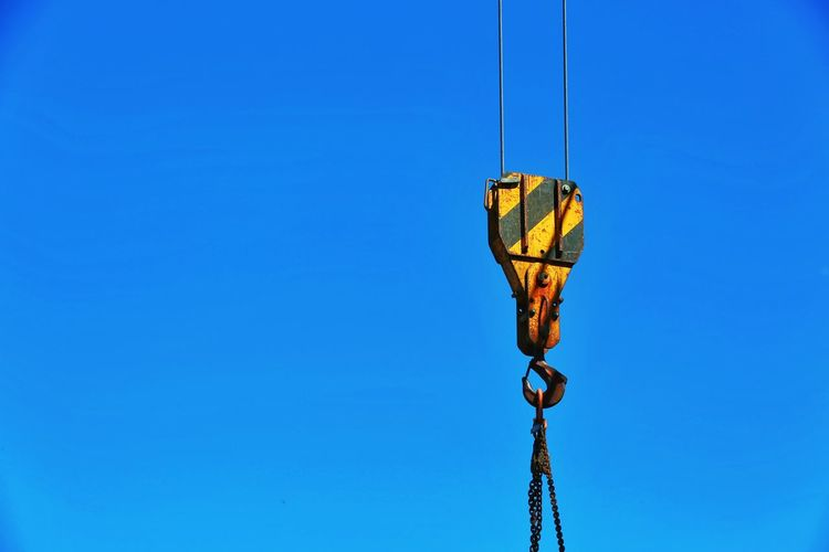 Low angle view of crane hook against clear blue sky