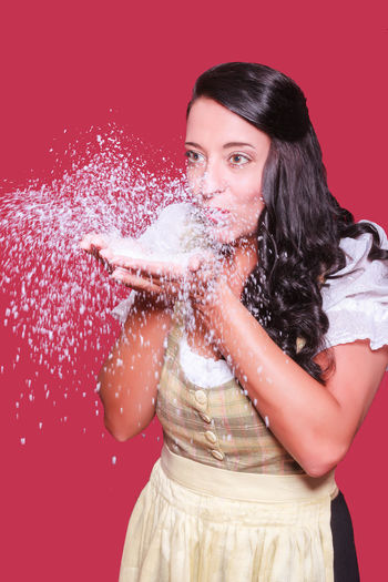 Beautiful young woman blowing artificial snow against red background