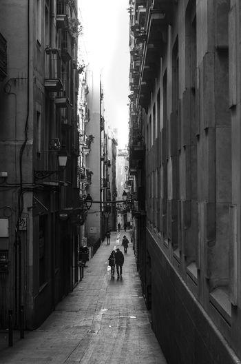 Man on cobblestone street in city against sky