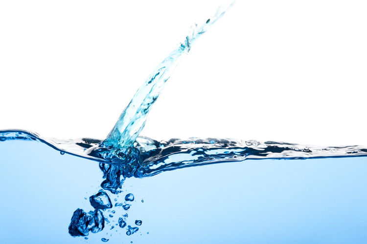 Low angle view of water splashing against blue background