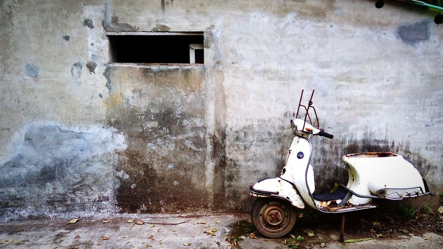 Side View Of A Scooter Against The Wall