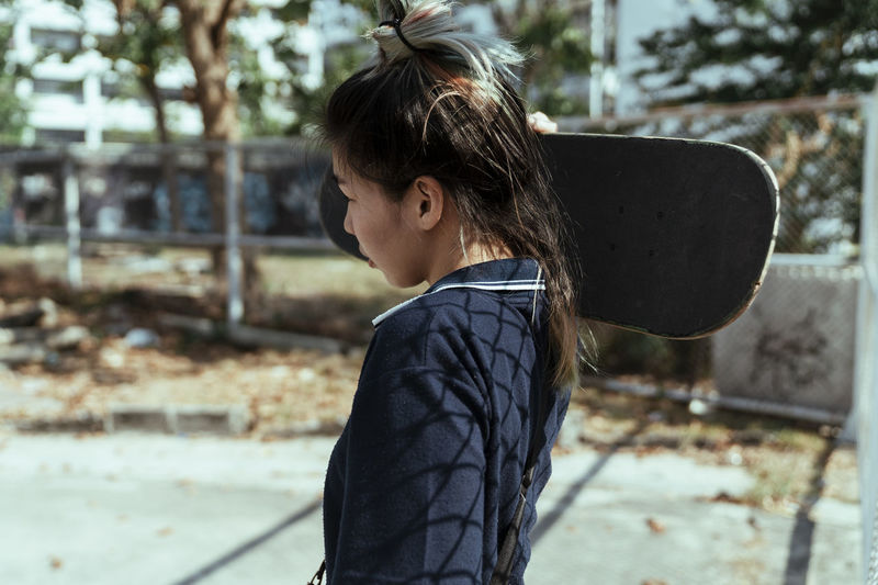 Side view of woman carrying skateboard
