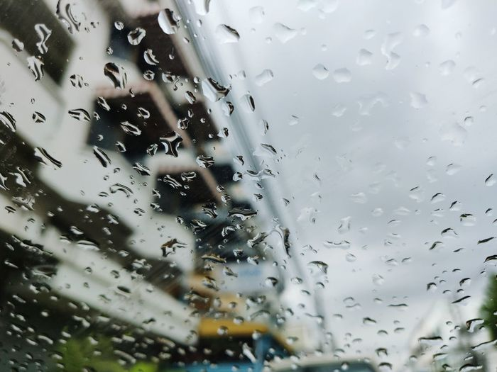 Full frame shot of wet glass window in rainy season