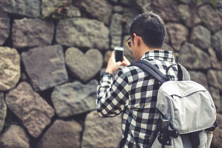 Man Wearing Backpack While Using Mobile Phone Against Rock Wall