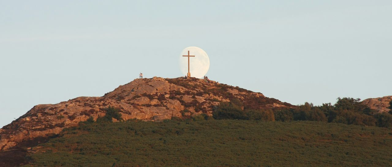 Photo-bombed by the Moon. Moon Cross Hilltop Juxtaposition Small People Far Away