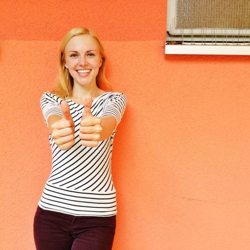 Portrait of smiling young woman gesturing thumbs up sign against wall