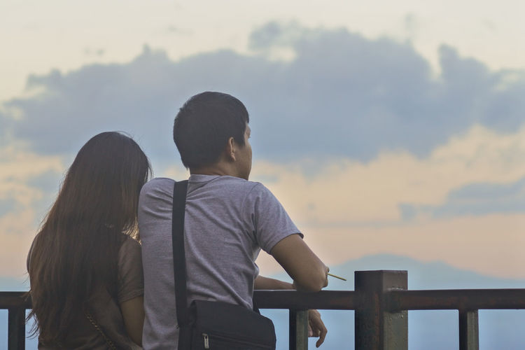 Rear view of couple standing against sky during sunset
