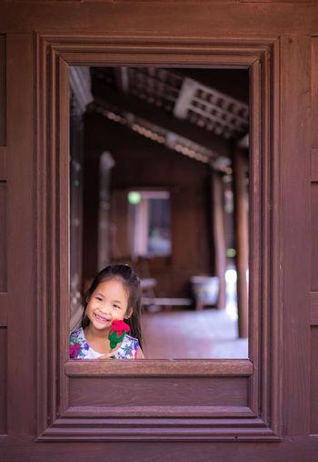Cute girl looking through door
